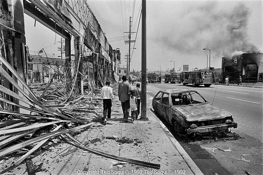 A group of children walk by riot damaged businesses on w.Adams Blvd. in South Los Angeles. 5/1/1992<br /> <br /> Images from the 1992 LA Riots.<br /> Photography by Ted Soqui &copy; 1992 <br /> <br /> Los Angeles has undergone several days of rioting due to the acquittal of the LAPD officers who beat Rodney King.<br /> Hundreds of businesses were burned to the ground and over 55 people have been killed.