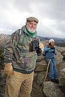 Senior man holding binoculars in mountains