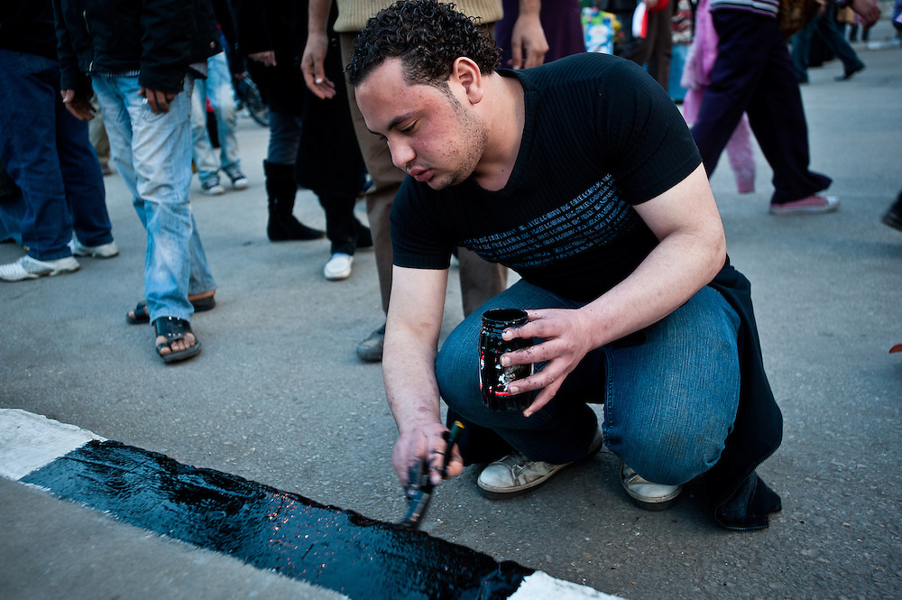An Egyptian volunteer repaints the sidewalk in Tahrir Square the day after protesters successfully brought about the resignation of President Hosni Mubarak, who ruled the country for thirty years. Volunteers flooded the square on Saturday; they repainted the sidewalk markings, swept and scrubbed the streets, and collected garbage until late in the evening.
