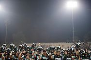 The Irvine High football team holds up their helmets as the band plays the school's alma mater at the end of Friday's playoff loss to Westminster.