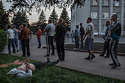 """Krasnoarmisk, Ukraine - May 11, 2014: A pro-Russian demonstrator lies dead on the grass as a group continues arguing with armed pro-Ukrainian militiamen of """"Dnepr Brigade"""" from Dnepropetrovsk, in front of the administrative building in central Krasnoarmisk, some 75 kilometers northwest of Donetsk, eastern Ukraine. One pro-Russian demonstrator died and another, seriously injuried, was evacuated after being shot in the chest while throwing stones towards """"Dnepr Brigade"""" members. CREDIT: Photo by Mauricio Lima for The New York Times"""