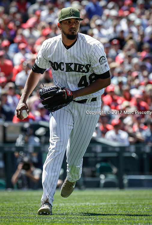 SHOT 5/28/17 1:28:37 PM - Colorado Rockies starting pitcher German Marquez #48 picks up a ground ball against the St. Louis Cardinals during their regular season MLB game at Coors Field in Denver, Co. The Rockies won the game 8-4. (Photo by Marc Piscotty / © 2017)