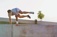 Young attractive man jumping on wall