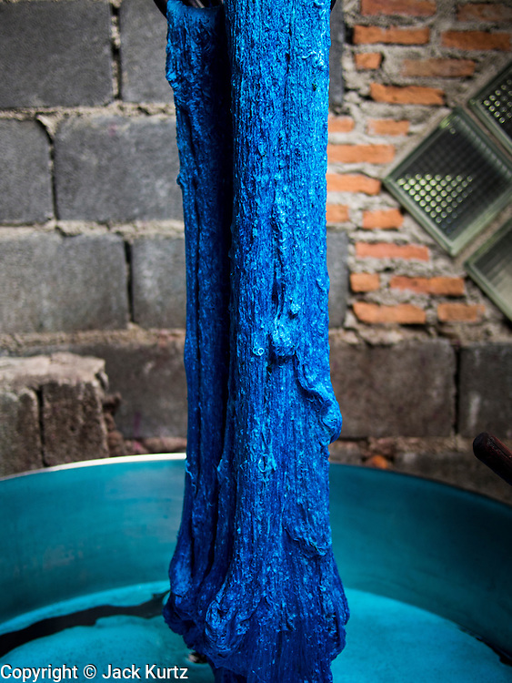 13 SEPTEMBER 2013 - BANGKOK, THAILAND: Thai silk threads come out of a vat of blue dye in workshop in a home in the Ban Krua section of Bangkok dyes silk threads. After the threads are dyed they are woven into silk. Many of the silk making families in Ban Krua are Cham Muslims from Cambodia who settled in Bangkok in the early 19th century after Rama I, the King of Siam at the time, offered them land in exchange for their services in a war against the Khmer (Cambodia) empire. The late Jim Thompson, founder of Jim Thompson Thai Silk, first made the silk weavers famous when he bought most of his silk from them.         PHOTO BY JACK KURTZ
