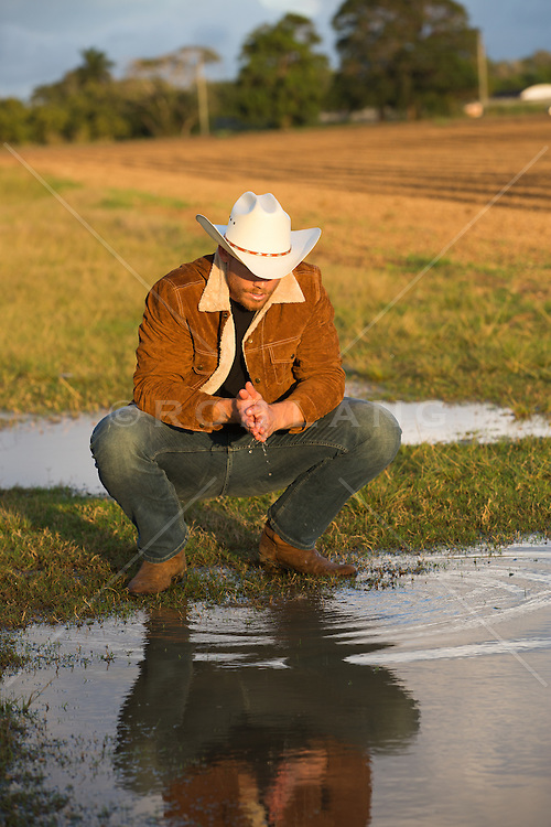 cowboy kneeling down by water on a ranch at sunset