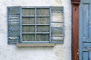 Very deteriorated window with door post.