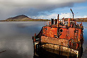 Wrecked ship in Ballinakill Bay, near Letterfrack, Connemara, Galway, Ireland, with Tully Mountain in the background.
