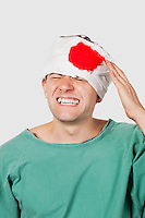 Young male patient with serious head injury against gray background