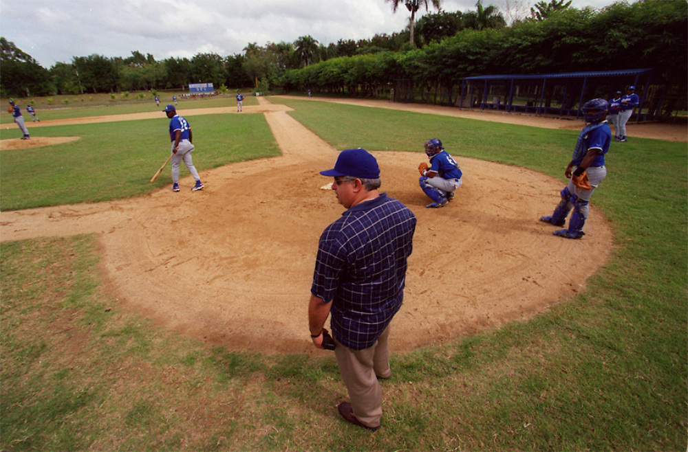 024221.SP.0115.dodgers4.kc--Guerra, Dominican Republic--Dodgers Campos Las Palmas, Director Pablo Peguero watches infield practice. This is the resort like baseball Academy where players get their chance to become professional baseball players. The overall atmosphere is very plush, where workers wear the Dodgers logo and every field meticulously manicured.  The players are living a life far different from their upbringing for many of the young players this is a chance of a lifetime.