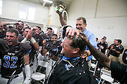 09/20/2014 - Somerville, Mass. - Head coach Jay Civetti gets a champagne bath from receivers coach Tony Fucillo in the locker room after Tufts' 24-17 win over Hamilton at Zimman Field on Sept. 20, 2014. The win snapped a 31-game losing streak. (Kelvin Ma/Tufts University)