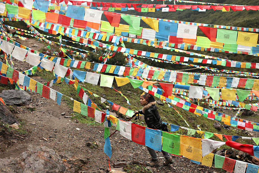Prayer flags mark the path approaching Shenpu, Buddha's Tears Waterfall, Yunnan, China; September, 2013.
