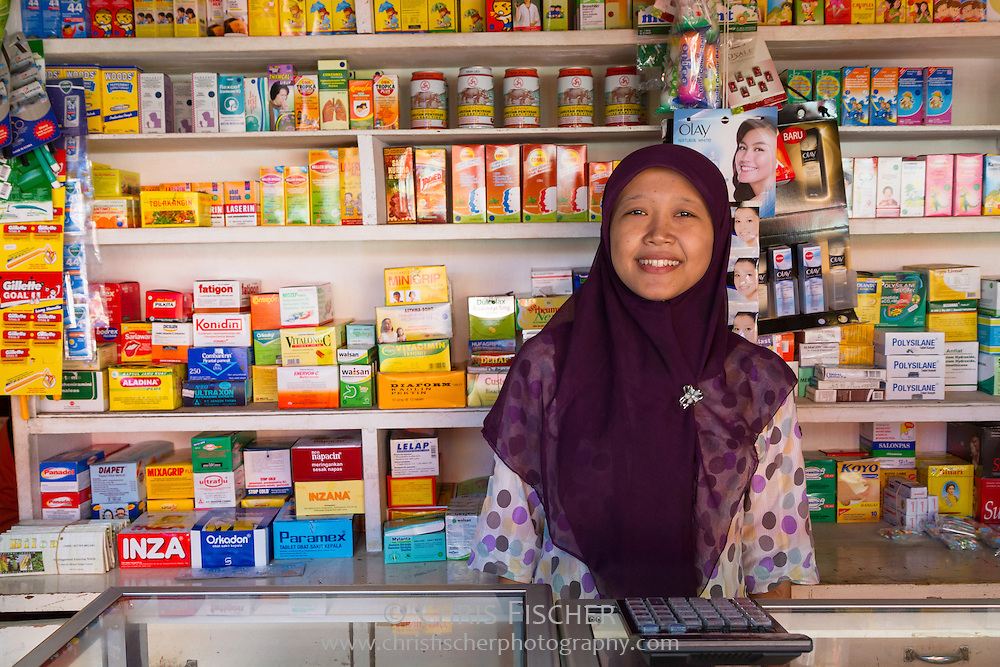 Smiling female Indonesian pharmacist at a pharmacy in Cianjur, West Java, Indonesia.