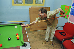 Man with learning disability playing game of pool in community centre,