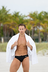 hot man on the beach in a speedo and a towel
