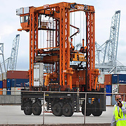 Nederland Zuid-Holland Rotterdam  27-08-2009 20090827 Foto: David Rozing .Serie over logistieke sector.ECT Delta terminal in de haven van Rotterdam. Telescopische spreader voertuigen vervoeren de containers op de terminal naar de vrachtwagens voor verder transport. Op de voorgrond een medewerker van ECT die toezicht houdt op veiligheid en regels op de terminal. .ECT,European Container Terminals, at the Port of Rotterdam. Europe's biggest and most advanced container terminal operator, handling close to three- quarters of all containers passing through the Port of Rotterdam. ECT is a member of the Hutchison Port Holdings group (HPH), the world biggest container stevedore with terminals on every Continent. At the ECT Delta Terminal telescopic spreader vehicles transport the containers between ship and stack / trucks.  Terminal operations are highly automated for discharging and loading large volumes...Holland, The Netherlands, dutch, Pays Bas, Europe .Foto: David Rozing