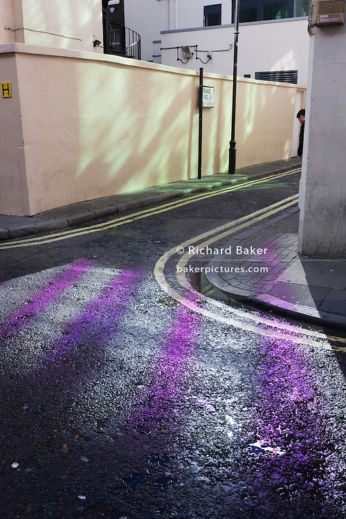 Pedestrian in a Soho side-street, pattened with purple.