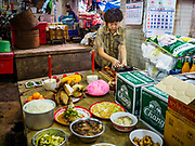 """05 SEPTEMBER 2017 - BANGKOK, THAILAND:  A woman sets up her Hungry Ghost Day banquet in a market in Bangkok's Chinatown. The Ghost Festival is a Buddhist and Taoist holy day celebrated on the 15th day of the 7th lunar month. It is primarily celebrated in China and Chinese communities outisde China. In Thailand, it's celebrated in Thai-Chinese communities in Bangkok, Phuket and Chiang Mai.  On that day ghosts and spirits, including those of the deceased ancestors, come out from the lower realm to visit the living. Families prepare elaborate banquets for the spirits and burn """"ghost money"""" for the spirits to use in the other realm. It is a day for venerating dead relatives.     PHOTO BY JACK KURTZ"""