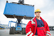 Confident male worker standing in front of freight vehicle at shipyard