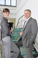Business man and woman on stairs in office building portrait