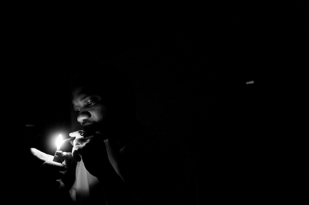 """Big Rickie lights a """"Backwoods"""" during a 48-hour blackout in Gary, Indiana.  Big Rickie works as a barber in Gary and is working on building his rap music collective """"Addictive Music.""""  (© William B. Plowman/Redux)"""