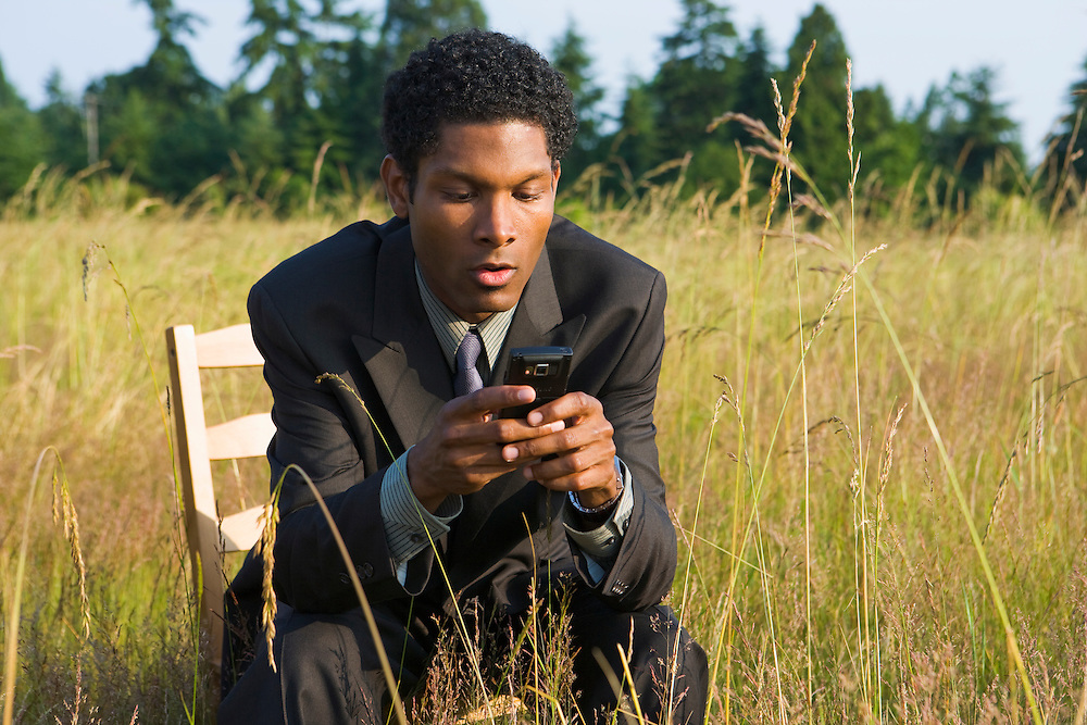 African American businessman sitting outside on a chair in a field of tall grass working with his wireless cell phone PDA / Blackberry.