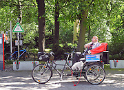 Berlin, GERMANY.   Rickshaw style Cyclist, relaxes in the sun, before his next customers, in the ground surrounding the Reichstag, Sunday  01/05/2011 [Mandatory Credit; Peter Spurrier/Intersport-images] Street Photos
