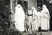 western woman posing with chador covered Moroccan women 1930s