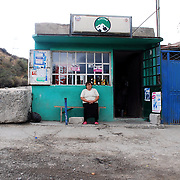 A woman sitting outside a shop at the entrance of Variani Village in the outskirts of Tskinvali, the capital city of the independent region of South Ossetia in Georgia.