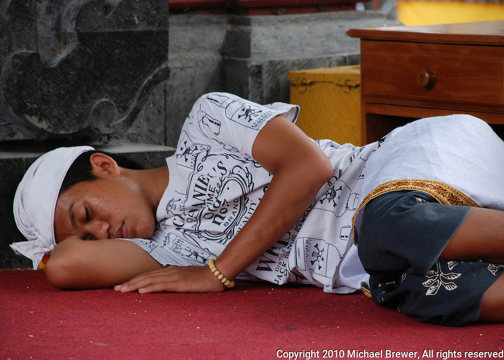 Boy sleeping on the floor of the temple in Bali, Indonesia.