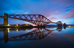 North Queensferry, Scotland, UK. 18 March , 2019. Soft pink light one hour before sunrise highlights the clouds above the Forth Bridge on a calm windless morning at North Queensferry in Fife, Scotland.