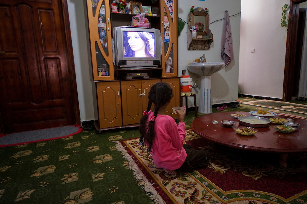 Aicha's youngest sister an Egyptian movie on television while having her lunch. Egyptian programmes are widely watched and liked by most people in Yemen.