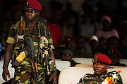 "A soldier stands guard by Guinea's president Captain Moussa Dadis Camara (right) during an official visit at the Kofi Annan private university in Conakry, Guinea on Thursday March 5, 2009. Camara, who took power after a coup in December 2008, was visiting the university to ""meet the youth"", as part of his efforts to solidify his support from Guinea's population.(Olivier Asselin for the New York Times)"