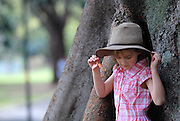 Child (6 years old) playing near trunk of Moreton Bay Fig Tree. The Domain, Sydney, Australia