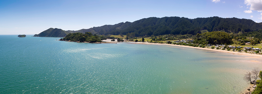 High-angle panoramic view overlooking Ligar Bay, with Abel Tasman National Park in the background.