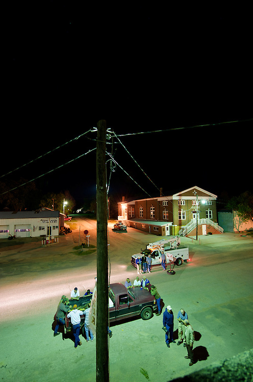 Residents of Cuba, Kansas gather to see the effects of lighting in their community of some 200 people.  The local utility company offered to help by turning out the lights in the whole town so that the contrast between normal street lighting and dark skies could be seen in this town in the sparsely populated area of north central Kansas. The gas station is on the left and the community hall is on the right.