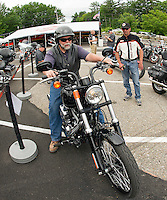 Mike Caron of Winterport, ME takes to the road on a Blackline assisted by Mark Lucas at the Harley Davidson free demo ride setup located in Meredith at the Hart's Turkey Farm parking lot.   (Karen Bobotas/for the Laconia Daily Sun)