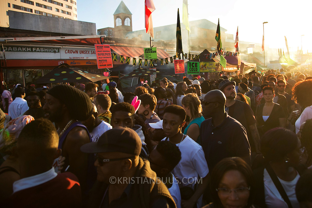 Carnival crowds gather in Ridley Road at the end of the carnival in the dying sun in East London, United Kingdom,Sept 11 2016. The annual Hackney Carnival took place on a hot summers day and the procession of dancers dressed in various outfits moved through the streets to much joy of the many bystanders. )