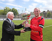 Dundee Thistle captain Damien Coogan is presented with the cup by referee's secretary Brian Connelly after Thistle beat DUMS in the Dundee Saturday Morning Football League Ross Kirk Memorial Cup Final at GA Arena<br /> <br />  - &copy; David Young - www.davidyoungphoto.co.uk - email: davidyoungphoto@gmail.com