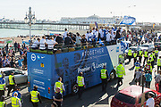 Open top bus heads towards Brighton Pier surrounded by fans during the Brighton & Hove Albion Football Club Promotion Parade at Brighton Seafront, Brighton, East Sussex. United Kingdom on 14 May 2017. Photo by Ellie Hoad.