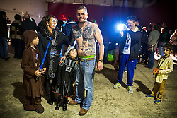 "© Licensed to London News Pictures . 06/12/2015 . Manchester , UK . Dad NEIL PARRY (40 from Mold in N Wales) with his extensive Star Wars tattoos , surrounded by family - son LUKE (nine) , wife FAY (38) and daughter LILY (six) . Fans attend Star Wars exhibition "" For the Love of the Force "" at Bowlers Exhibition Centre in Manchester . Photo credit : Joel Goodman/LNP"