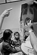 TEN, 5 Jahre alt, einen Tag, nachdem sie in BAAN GERDA eingeliefert wurde, hat man sie in das Provinz Hospital von Khok Samrong zur Untersuchung geschickt. Der behandelnde Kinderarzt hat sie aufgrund der Tuberkulose und der Lungenentzuendung und des labilen Gesundheitszustandes gleich auf die Krankenstation verlegt. Die Pflegemutter JAI ist bei ihr und versucht die kleine Ten zu beruhigen. .Provinz Lop Buri, Thailand....