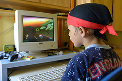 Five year old boy playing a PC video racing game in his bedroom wearing a pirates bandana and an England sports t-shirt,