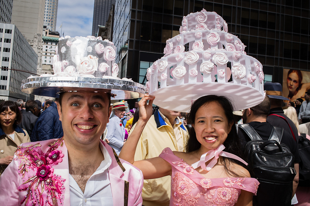 New York, NY - 21 April 2019. A  couple with ornate wedding-cake hats at the Easter Bonnet Parade and Festival on New York's Fifth Avenue.