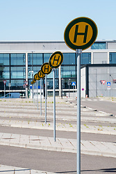 View of empty bus stops and signage at Berlin Brandenburg Willy Brandt Airport Terminal uncompleted and 7 years behind schedule in Berlin Germany