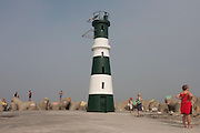 Shipping watchers beneath the lighthouse on Paredao da Praia da Barra, Costa Nova, Aveiro, Portugal.