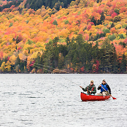 Two men fly fishing from a canoe on Greenough Pond in Wentworths Location, New Hampshire. Fall. Northern Forest.