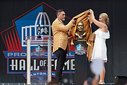 Aug 3, 2019; Canton, OH, USA; Kevin Mawae (left) and wife and presenter Tracy Mawae unveil bust during the Pro Football Hall of Fame Enshrinement at Tom Benson Hall of Fame Stadium. (Robin Alam/Image of Sport)