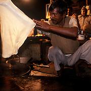 A man prepares a giant Halwa paratha. New Delhi, December 2003