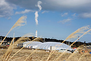 Workers carry equipment into the giant greenhouse domes at the Minamisoma Agri-Solar Park in Minamisoma, Fukushima, just 25 km from the Daiichi plant. More than 2,000 solar panels will power the  domes, inside which farmers affected by the 2011 tsunami and nuclear accident will be able to grow produce.  .Photographer: Robert Gilhooly