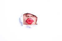 View of red puckered lips through paper hole